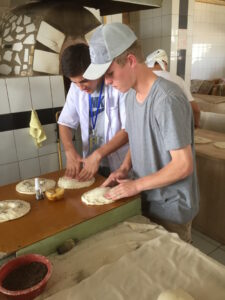 Wil Jorgensen steps in to prepare dough for Naan at a bazaar in Tashkent, Uzbekistan