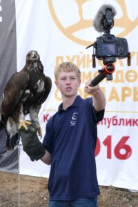 Wil Jorgensen has a trained eagle on one arm and shoots video with the other at the World Nomad Games