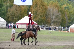A boy balancing on the shoulders of two riders thunders through the World Nomad Games site