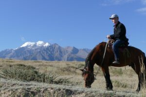 Wil Jorgensen on horseback with the Tian Shan Mountains in the background.