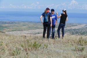 Katie Tackman, left, and Sarah Lindell chat with Kuban Zholdosh, a trekking operator in Barskoon, Kyrgyzstan