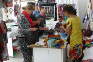 Katie Tackman, Tom Warren and Josh Jorgensen buying treasures in Samarkand