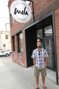 Kyle Hendrickson in front of the Mela Roasting and shipping operation on Orondo St.