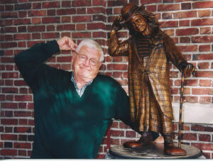 The late Paul Pugh with the statue in his honor that is located in front of the Wenatchee YMCA