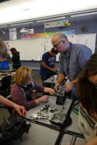 Teacher Darrell Moser helps a student dismantle part of a small engine at Orchard Middle School